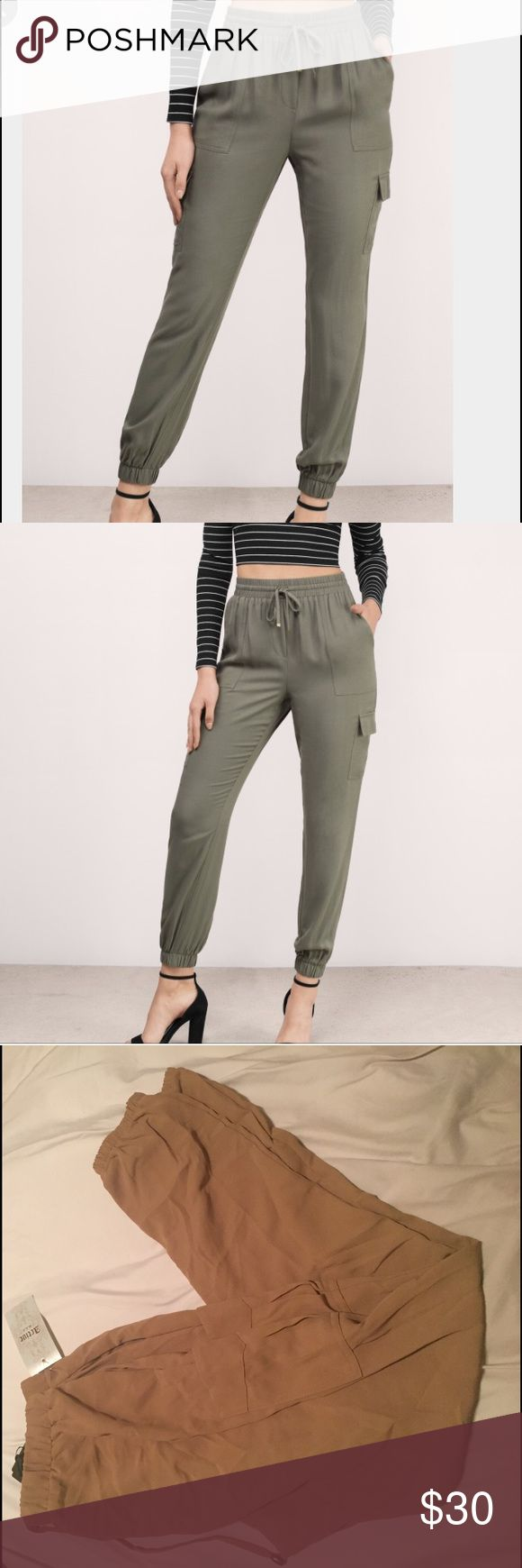 "Khaki jogger pants Add Joggers to your closet. Featuring a side patch pocket. Pair with a bodysuit and heels. Polyester  Dry Flat Waist: 28""/71.1cm Length: 40""/101.6cm Inseam: 29.5""/74.9cm Front rise: 10.5""/26.7cm Back rise: 13.5""/34.3cm At leg opening (Elastic): 10""/25.4cm Side pockets Self tie waist fastener Measured in size Small Pants Track Pants & Joggers"