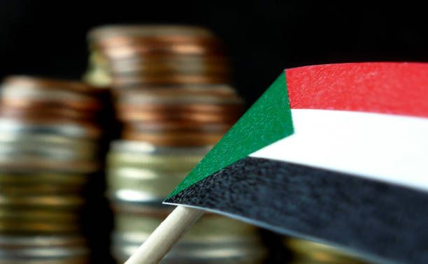 sudan flag waving with stack of money coins macro