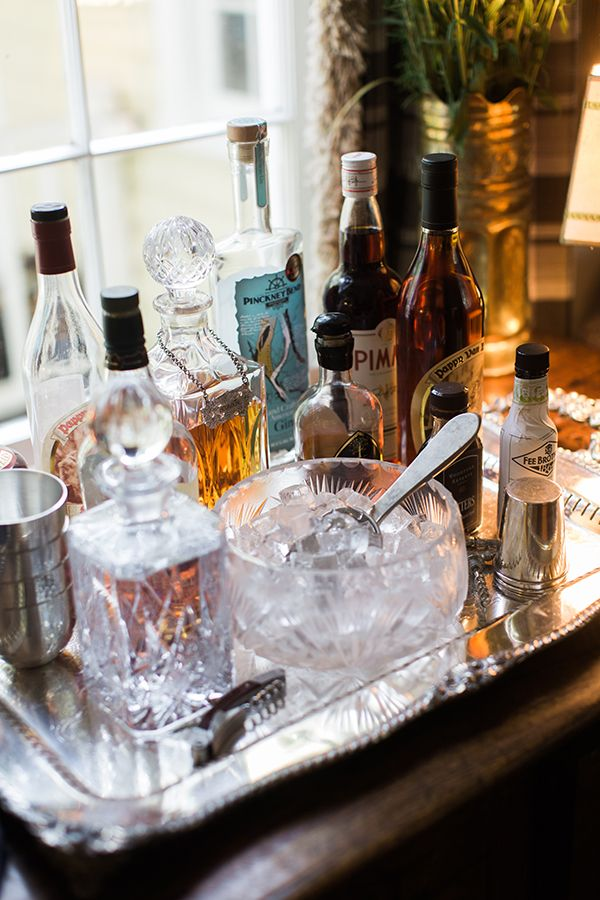 Classic tabletop home bar setup with crystal decanters and ice bowl on traditional silver tray.