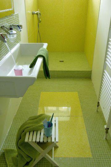 Une salle de bains verte du sol au plafond