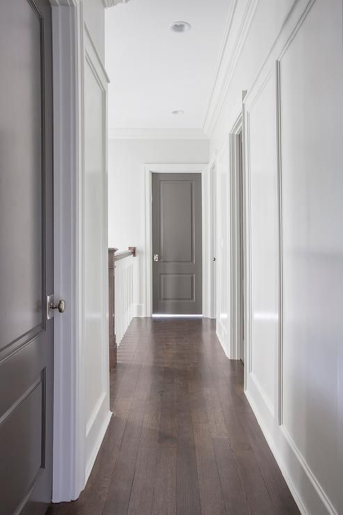 Chic hallway features white walls fitted with gray paneled doors adorned with polished nickel door ...