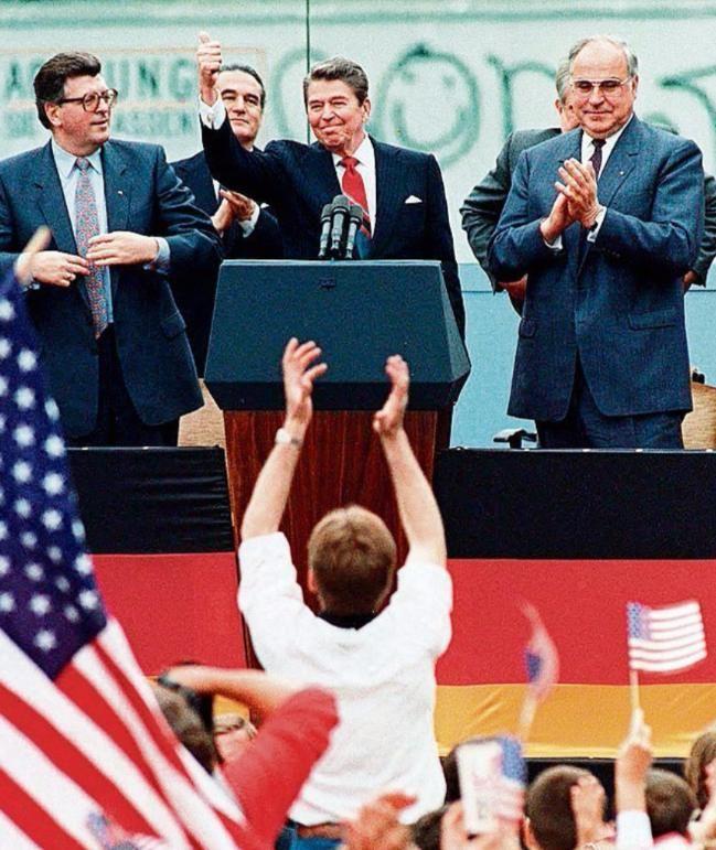 Ronald Reagan bei seiner Rede vor dem Brandenburger Tor, die den ersten Riss in der Berliner Mauer markierte (zwischen Bundeskanzler Helmut Kohl und Parlamentspräsident Philip Jenninger)