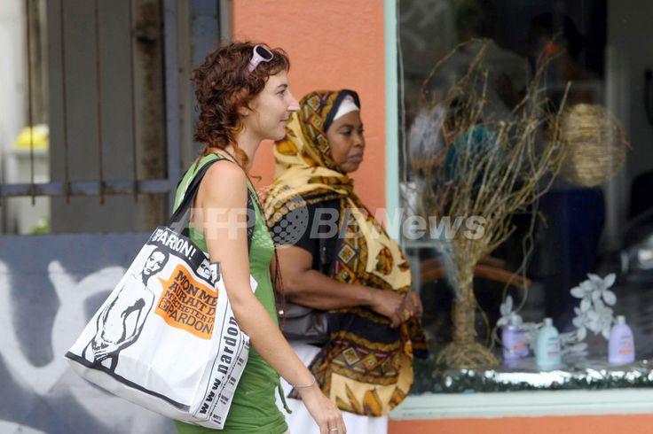フランス海外県・レユニオン(Reunion)の県都サンドニ(Saint-Denis)でカーラ・ブルーニ(Carla Bruni)仏大統領夫人のヌードがプリントされたバッグを持つ女性(2008年12月12日撮影)(c)AFP/RICHARD BOUHET ▼13Deb2008AFP|ヌード写真を勝手に使わないで!仏大統領夫人が訴え http://www.afpbb.com/articles/-/2549405