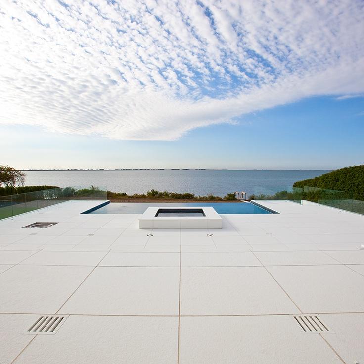 beautiful sleek modern glass thassos example on a pool deck.