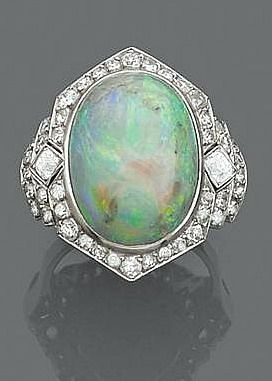 Art Deco era ring opal It is decorated with an oval opal bezel set in a diamond pattern accented with diamonds brill size.