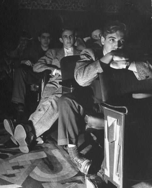 The local movie theater, boys have a very difficult time finding a place to put their long legs. Des Moines, June 1945 by Nina Leen
