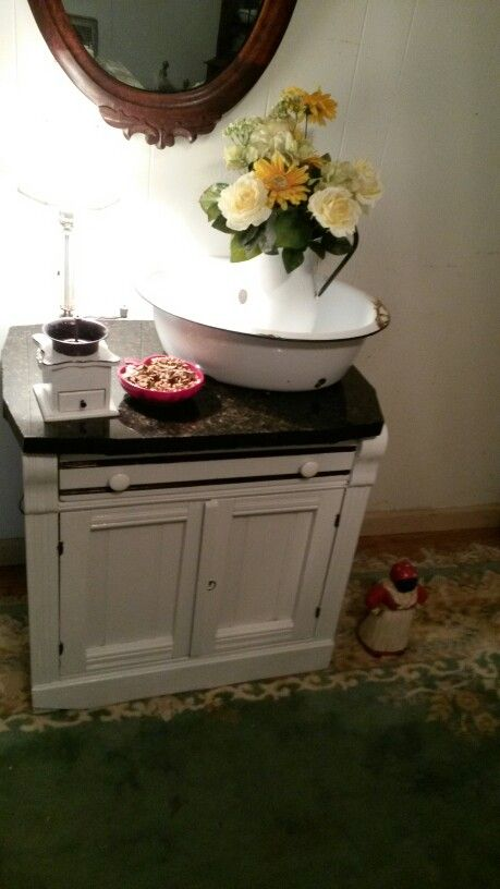Found this poor little wash stand in the trash pile. It was horrible looking but it had potential. I sanded it down and painted it wjite to match a hoosier cabinet. The top was beyond saving so we purchased a pice of marble for it.  So happy with the outcome