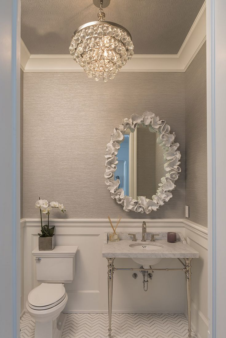 Hamptons house half bath featuring Robert Abbey for the bling chandelier, Kallista for the marble sink, Made Goods for the white coral mirror, Trowbridge Gallery for the black & white photos and New Ravenna Mosaics for the chevron white calacatta marble floor #SusanGlickInteriors #luxury #modern #bathroom