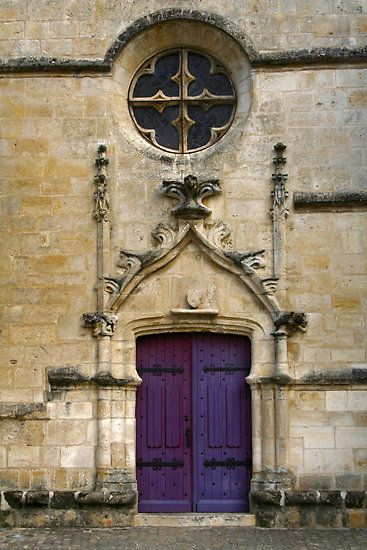 Purple church doors of the 16th century church by Marais Poitevin in the town of Coulon, France