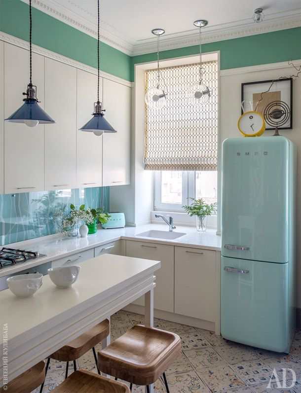 Фартук на кухне покрашен в тон холодильника SMEG, расписан вручную орнаментом, подобранным к росписи над барным столом, и защищен сверху прочным стеклом.