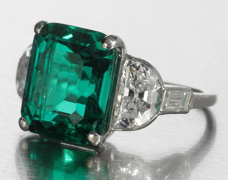 A fine art deco emerald and diamond ring, circa 1925  The cut-cornered step-cut emerald, weighing 8.41 carats, between demi-lune and baguette-cut diamond shoulders, diamonds approximately 1.85 carats tota