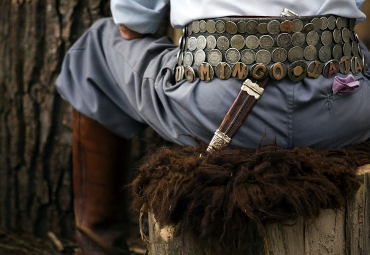A close up showing some of a gaucho's traditional clothing. The belt is called a riestra and is covered with coins. The leather boots and loose trousers (bombachas) are also made in the typical gaucho style. San Antonio de Areco is located 110km from the city of Buenos Aires and is known for it's colonial buildings and Gauchos, the cowboys of Argentina. Every Friday (weather permitting) a group of local Gauchos attend a Fogón, a meeting where they can talk, eat, drink and play traditional…