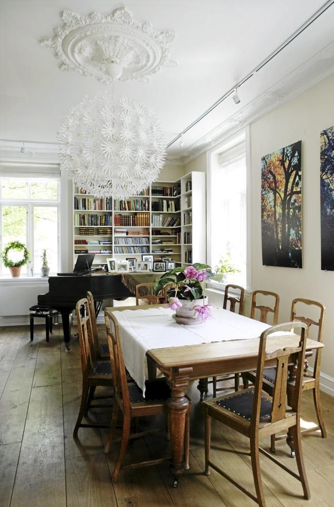 Det antikke spisebordet i jugendstil kan trekkes ut i det uendelige. Bildene på veggen er av trærne utenfor vinduet, og er tatt av eieren selv. Lampen i taket er den populære Maskros fra Ikea. I hjørnet mellom vinduene har litteratur og musikk fått sin plass, i form av bøker, CD-plater og et stort flygel.