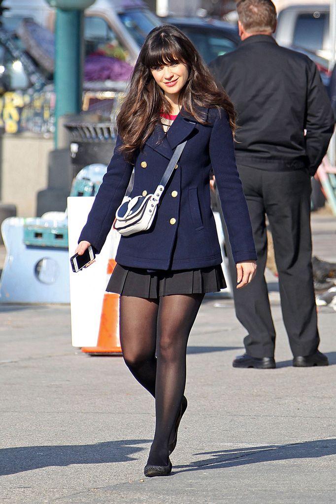 navy pea coat, crossbody bag, black pleated skater skirt, black tights, black ballet flats. zooey deschanel as jess day on the set of new girl