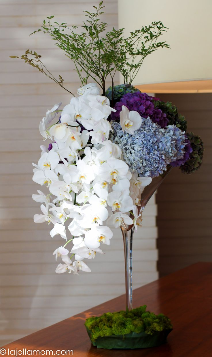 Orchids draped over the side of a martini glass-shaped vase with hydrangeas and greenery at @fshongkong