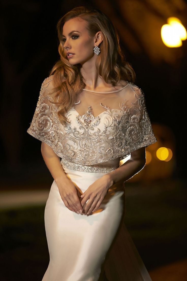 This sophisticated fit and flare gown accented with crystals beaded belt and removable capelet and illusion train with dramatic embroidery and beading embellishment. Fabric: Silk Mikado+Tulle. Available Color: Ivory, Diamond White