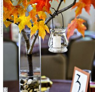 tall, square vases filled halfway with river rocks and  real branches of fall leaves are placed in all of them