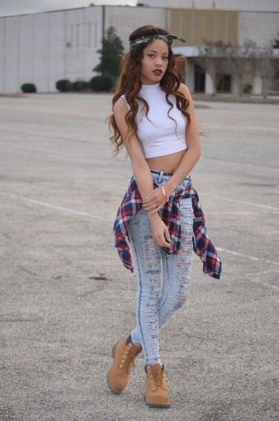 Ripped jeans with flannel and a crop top with timberlands.