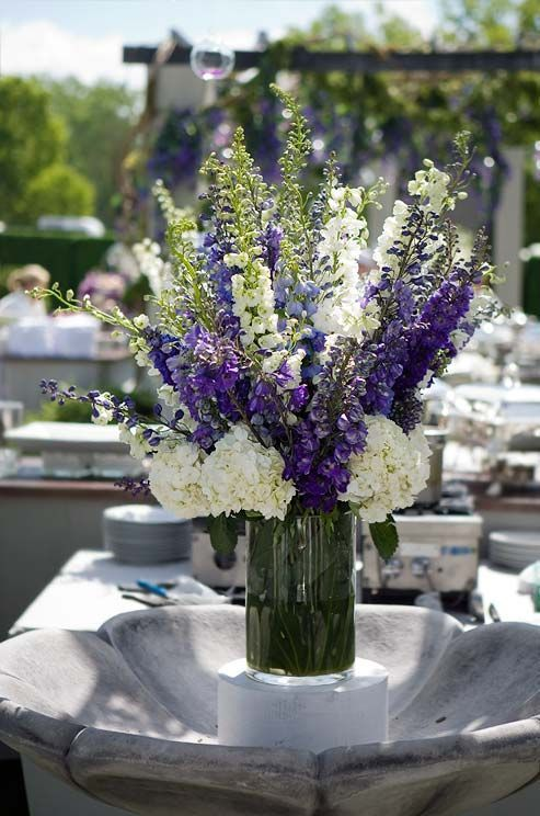 An arrangement of delphiniums expresses an open heart and playfulness, emitting a fun vibe at any reception.