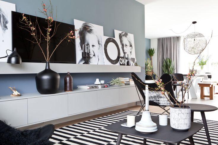 Leuk idee: de tv valt minder op doordat deze tussen grote zwart/wit canvasdoeken staat [vtwonen.nl].