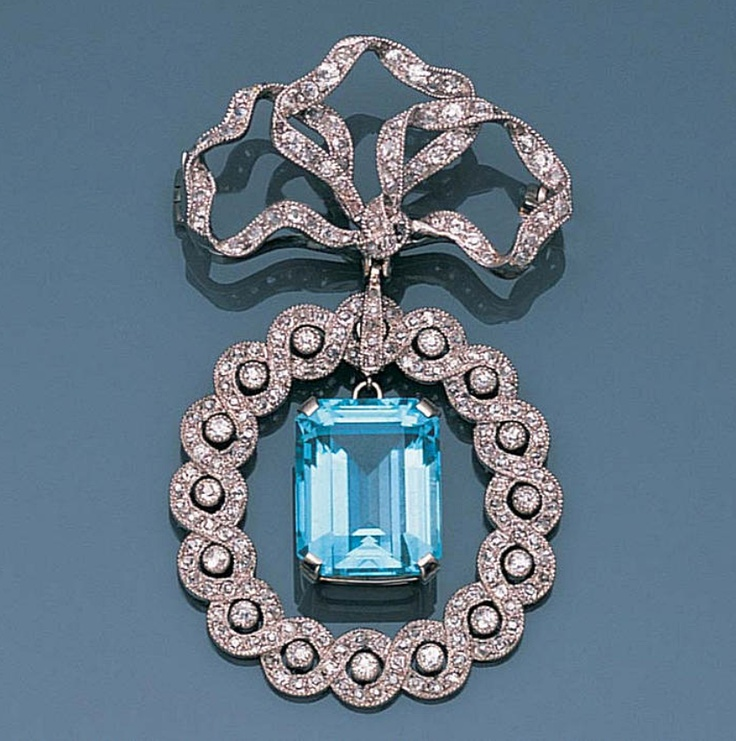 A belle époque aquamarine and diamond brooch, circa 1910  The fluttering ribbon bow surmount millegrain-set with brilliant-cut and cushion-shaped diamonds, suspending a central step-cut aquamarine pendant within an entwined ribbon border, pierced and millegrain-set with further cushion-shaped diamonds, length 5.5cm