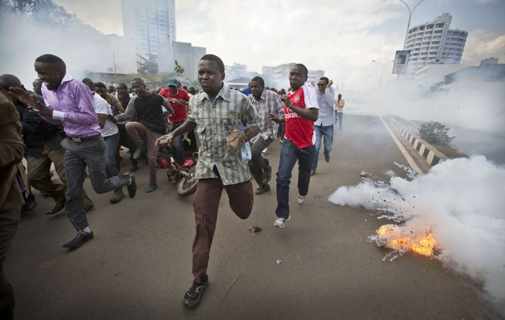 Photos capture the brutality of Kenya's police before the country's presidential election next year.  Opposition supporters, some carrying rocks, flee from exploding tear gas grenades fired by riot police.  Photography by Ben Curtis.   Imagine standing next by to these people, trying to get a shot.