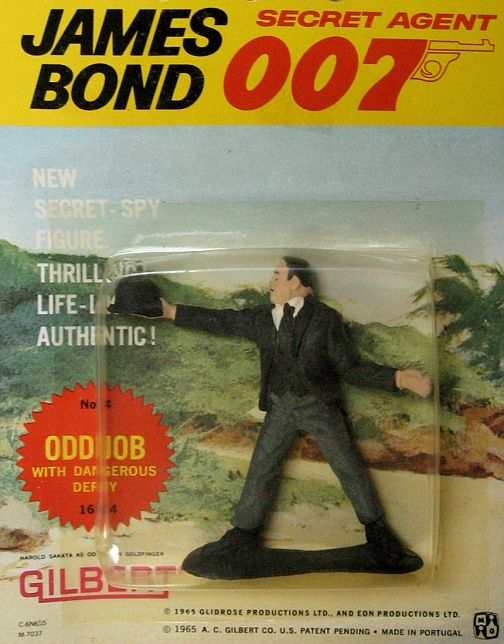 "Original 1965 James Bond ""Odd Job"" Action Figure, by Gilbert. AUTHENTIC 1965 figure of ""Odd Job"" whose hat, when thrown frisbee-style, became a DEADLY WEAPON! Remember that famous scene in ""Goldfinger"" where he throws it and beheads a marble statue?!! Anyway, this Odd Job is MINT ON SEALED CARD!! These Gilbert action figures and some of the toys and playsets they came out with in the same time period were among the FIRST OFFICIALLY-LICENSED JAMES BOND TOYS! Only one in stock. $75.00"