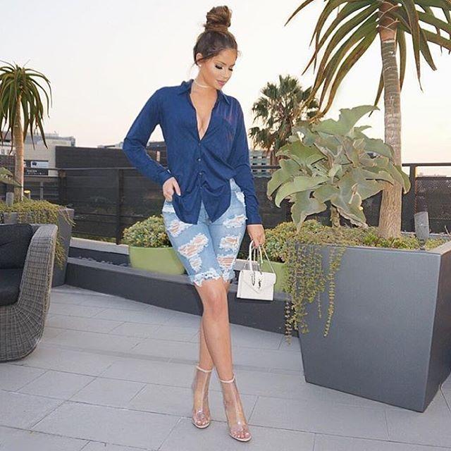 Olivia Pierson wears distressed denim Bermuda shorts and sheer booties.