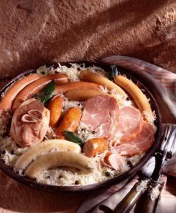 CHOUCROUTE (Pour 8 P : 2 kg de choucroute crue, 2 gros oignons, 200 g de graisse d'oie, 1 L de riesling ou 1 L de bière, 1 litre d'eau) (DANS 1 GAZE : 3 gousses d'ail, 2 clous de girofle, laurier, thym, 6 baies de genièvre et 12 grains de poivre) (GARNITURE : 1 palette de porc fumée, 1 jambonneau ½ sel ou 1 beau jarret de porc juste blanchi, 400 g de poitrine de porc fumée, 1 petit carré de porc fumé, 8 saucisses de Strasbourg)