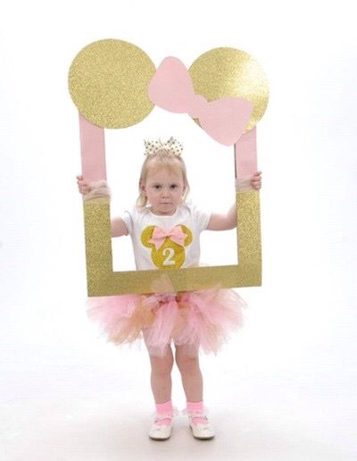 Minnie Mouse photo booth made from a big picture frame, scrapbooking paper, and tool.