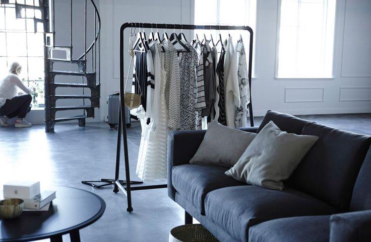 Eine Kleiderstange gefüllt mit hängender Kleidung neben einem Sofa und einem Couchtisch.