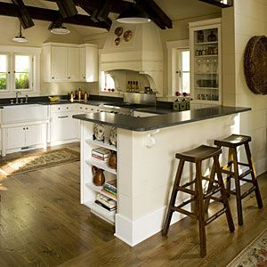Cozy Kitchen     Reclaimed heart-pine flooring flows from the adjacent dining room right into the cozy kitchen. Cabinets built in a whitewashed Shaker style provide a soothing contrast to dark-stained floors and wood trusses above.