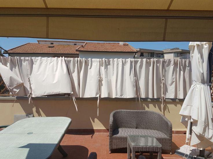 terrazza arredata con tenda a bracci e tende in tessuto acrilico manomorbida fermate con lacci sul grigliato