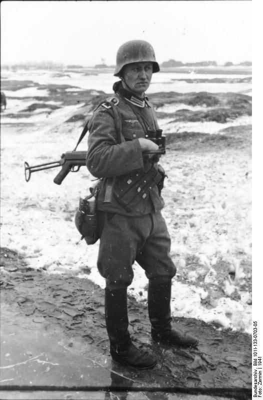 German Infantry NCO armed with an MP-40 sub-machine gun, Poland, 1941. He also carries a pair of Zeiss standard issue field glasses. *Note the leather SMG magazine pouch.