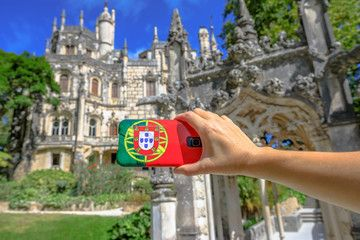 Woman takes photo of Regaleira Palace or Monteiro Palace by mobile phone with Portugal flag cover.Tourism and travel in Portugal.Quinta da Regaleira is a Unesco Heritage and popular landmark in Sintra
