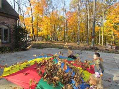 Tossing the leaves into the air - love this - would add little rakes so that they could rake the leaves into a pile and then put them on the parachute.
