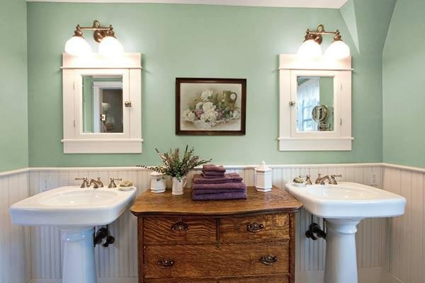 A vintage wooden dresser ties together the classic theme of this bath but provides a neutralizing contrast to the abundance of white and minty green. | Photo: Judith Bromley