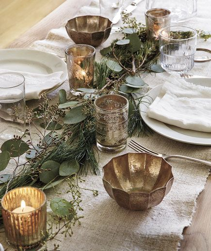 Dress up your table with a runner of white pine, seeded eucalyptus, boxwood, or other greens. It's an inviting arrangement that doesn't block conversations the way tall florals can. Layer clusters of leaves and sprigs—flatter ones first, shapelier ones on top—in a slightly undulating shape for a relaxed, natural look.