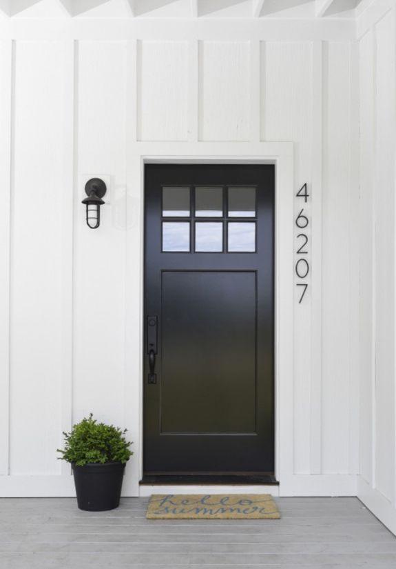 Black front door on white house, vertical street numbering, pot plant, black lantern, grey timber floorboards
