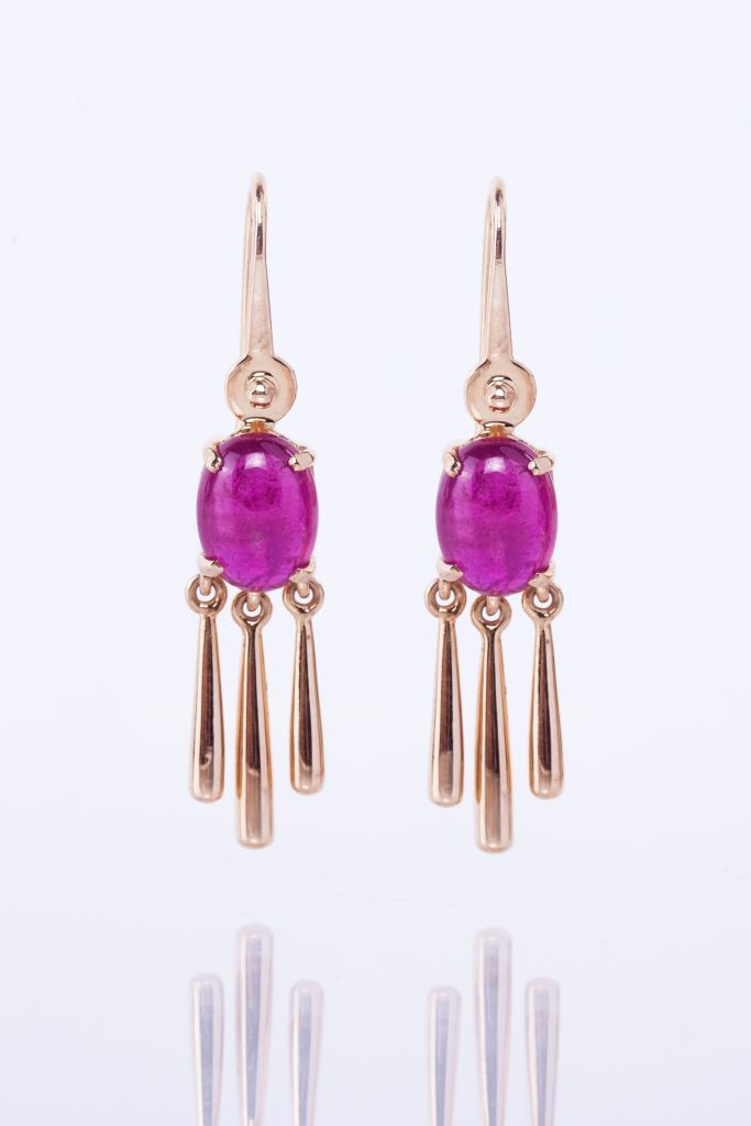 Ruby earring tassles  Designed to inspire a delicate playfulness, this pair of hook earrings features cabochon cut rubies handcrafted in 18 karat yellow gold.