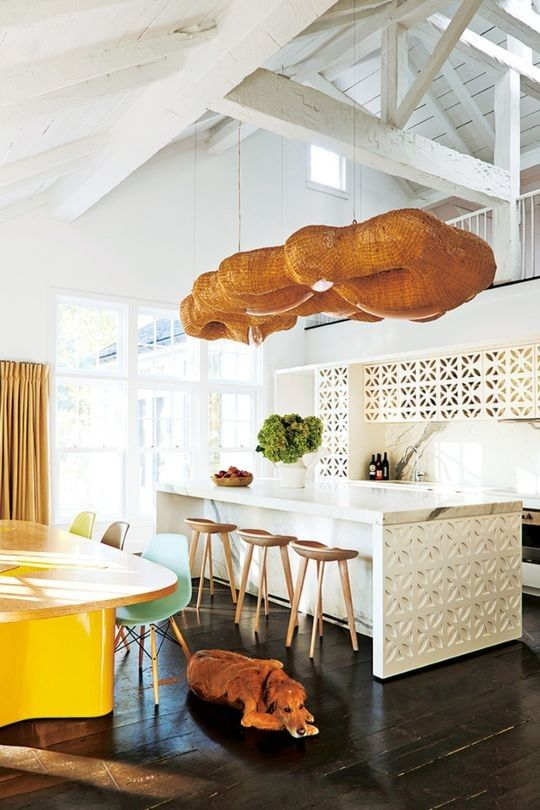 These are the most popular kitchens in Vogue Living - Vogue Living  |  India Mahdavi's feature light and table add spunk to this otherwise all-white kitchen. Plus who doesn't love a pooch?