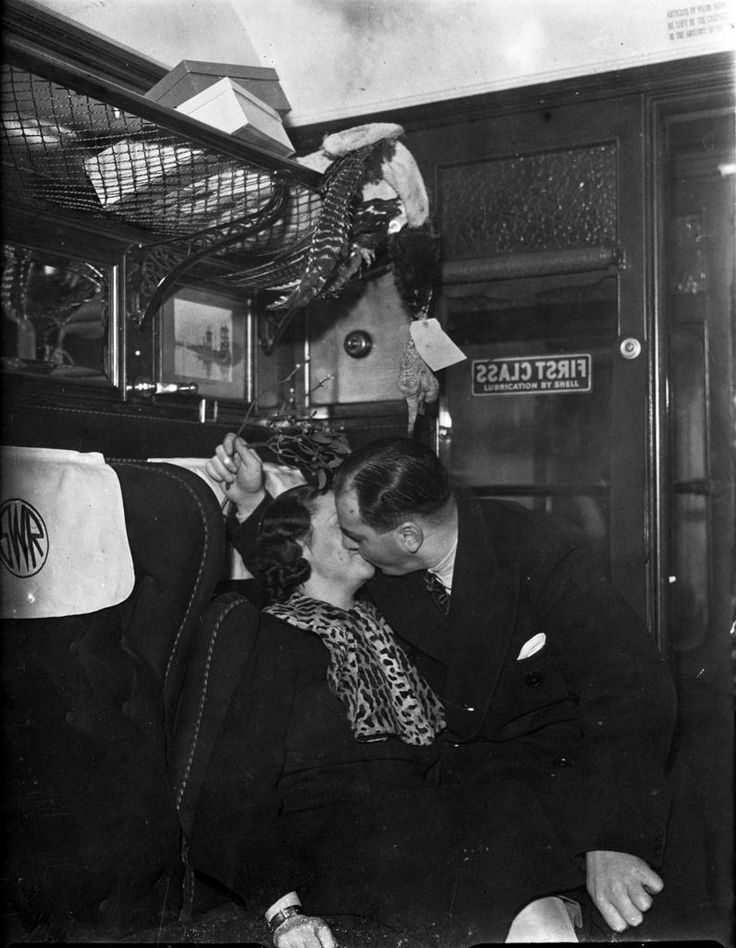 A Christmas kiss: A couple embrace each other under the mistletoe in a first class railway carriage at Paddington Station, London, 1936. (Photo by David Savill/Topical Press Agency/Getty Images)