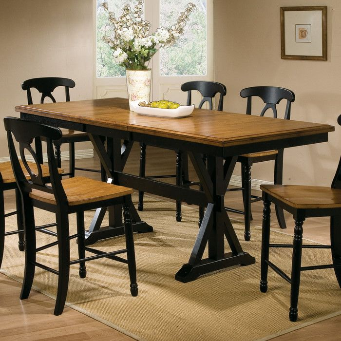 The Counter Height trestle table is constructed from solid Asian hardwood and features a self storing leaf and a unique trestle base. The finish is lightly distressed.