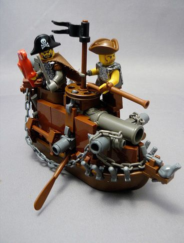 LEGO pirates on a small steamboat armed with cannons, a tiny flag, oars, chains, and a frog as the figurehead.