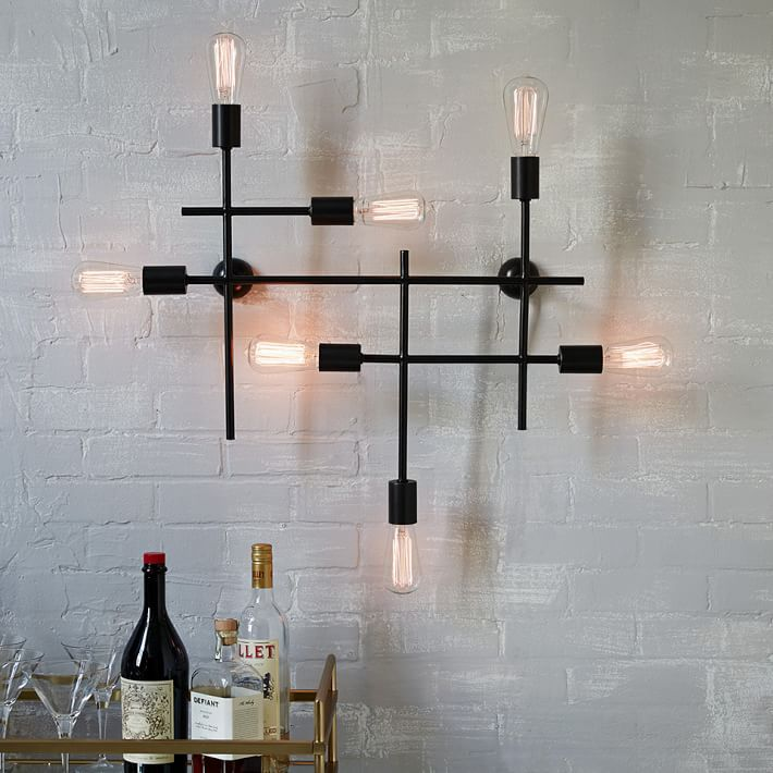 Industrial grid wall sconce above a headboard instead of side lamps
