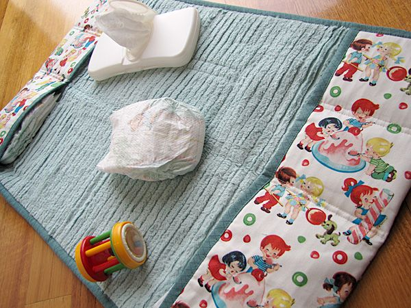 Terrific baby change mat with pockets, wish i had one of these when my little girl was born, with pdf instructions to make, Nicole Mallalieu is the talented artist who desinged it, see http://whipup.net/category/whipup-tutorials/ for info, 3/4 of the way down the page