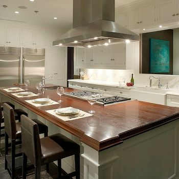 Fabulous Gourmet Kitchen Features A Ceiling Mount Vent Hood Suspended Over An Island Cooktop