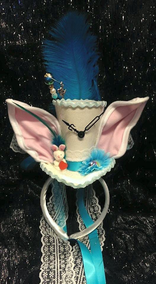 Wunderschöne kleine weiße Kaninchen inspiriert Mini Hut aus Alice im Wunderland in weißen Glitzer mit weißem satin Haarband. Eine schöne blaue Straußenfedern sitzt an Rückseite Hut mit weißen Spitzen & blauen satin Bänder gebunden um Zentrum in Schleife am Rücken die dann trail hinunter. Echte Metall Uhrzeiger sitzen vor der Hut mit weißen und rosa Hasenohren jeder Seite. Eine blaue Hahn Feder sitzt hinter einem kleinen süßen weiß & rosa Häschen hält ein rotes Herz. Ein blaues Gänseblümchen…