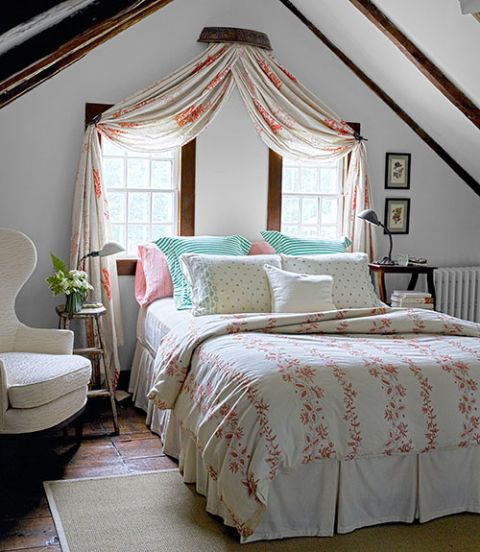 In the master bedroom of this Connecticut home, a vintage stool and ladder stand in as bedside tables. The coverlet is from Calypso, and the walls are painted White Dove by Benjamin Moore.