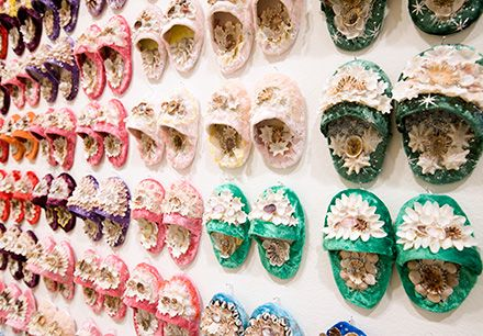 Shellworked slippers (2008) by Esme Timbery. Constructed from mixed media and adorned with shells, these tiny slippers exemplify traditional Indigenous craft practices of La Perouse, a headland on the shores of Botany Bay with a large Aboriginal population. They form a memorial to the Stolen Generations − Aboriginal children who were forcibly removed from their families and communities by government edict throughout the greater part of the twentieth century.